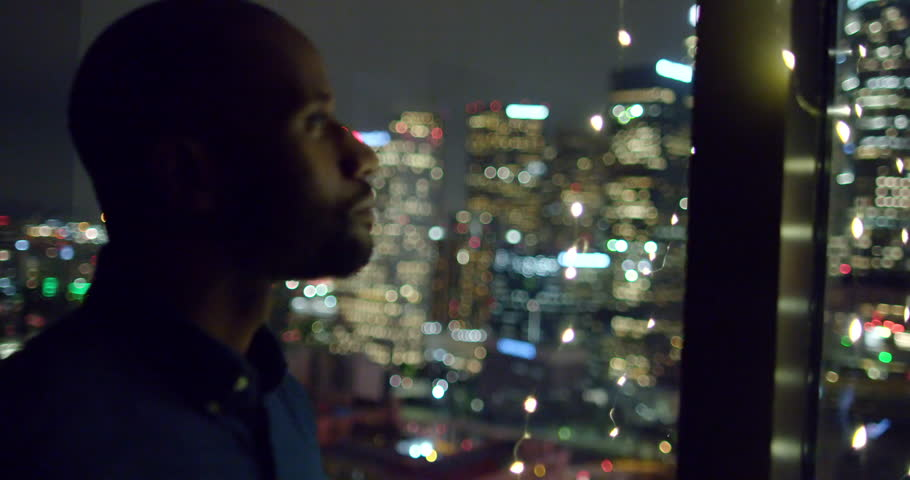 Dark skinned African American man sips from a wine glass in a window with city lights while looking out at Downtown Los Angeles at night. Medium close up, hand held.