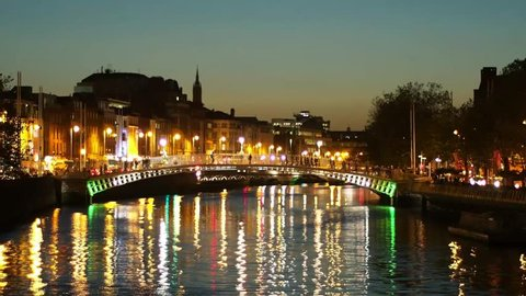 River Liffey and the famous Hapenny Bridge, night view cityscape, Dublin, Ireland. Yellow and green night lights are reflecting on the water surface. Christmas time in Europe.