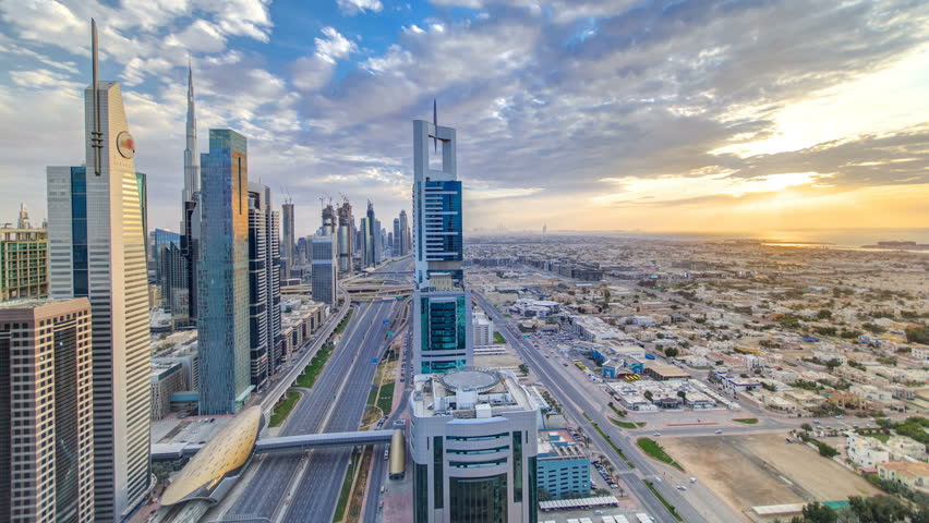 Dubai skyscrapers sunset timelapse evening time. Dubai Metro station and traffic on Sheikh Zayed Road. Aerial top view drom tower rooftop. Beautiful colorful cloudy sky