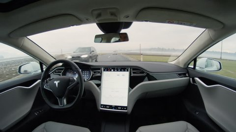 LINZ, AUSTRIA - FEBRUARY 2nd 2017: Passenger in the backseat of absolutely autonomous next gen self-driving Tesla car. A driverless car with upgraded avtopilot feature driving on countryside road