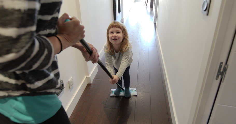 Funny scene of three years old laughing child sliding on flat dust mop while woman sweeping the floor in corridor at home  | Shutterstock HD Video #24560732