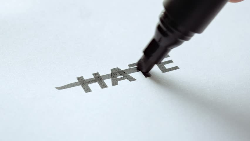 Man hand crosses out the word Hate with black marker. No Hate