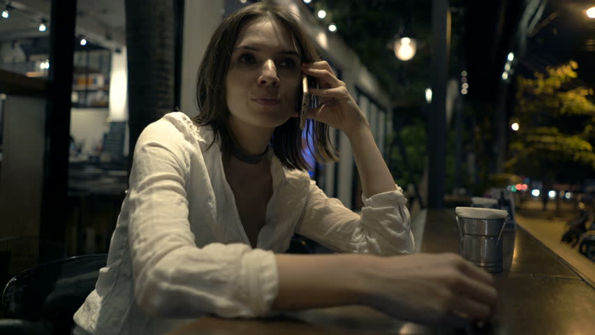 Upset woman talking on cellphone sitting in cafe at night  | Shutterstock HD Video #24602498
