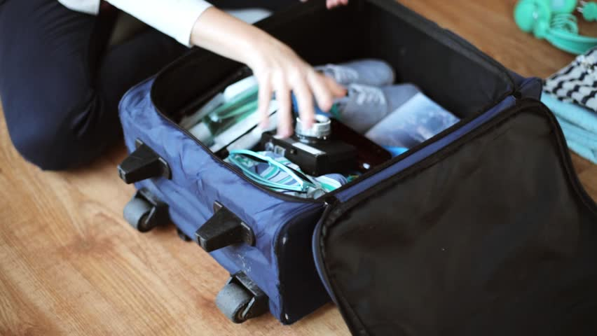 Tourism, people, luggage and clothing concept - hands packing travel bag with personal stuff   Shutterstock HD Video #24609908