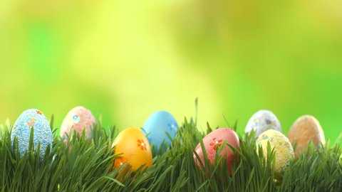 Easter colorful painted eggs on lawn grass over green blurred bokeh background. Spring Holiday nature scene. UHD video footage. Ultra high definition 3840X2160