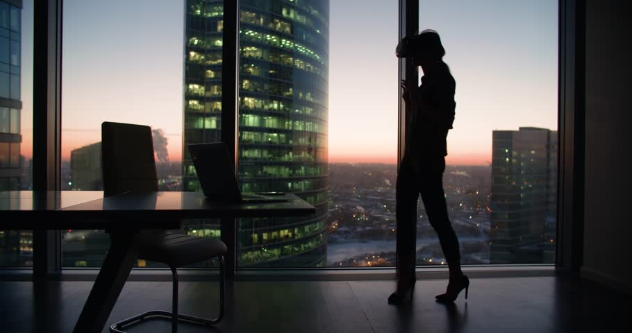 Silhouette Technology VR-businessman young girl wearing virtual reality technology VR Glasses to work in modern office in a skyscraper. the creation of the presentation | Shutterstock HD Video #24630848