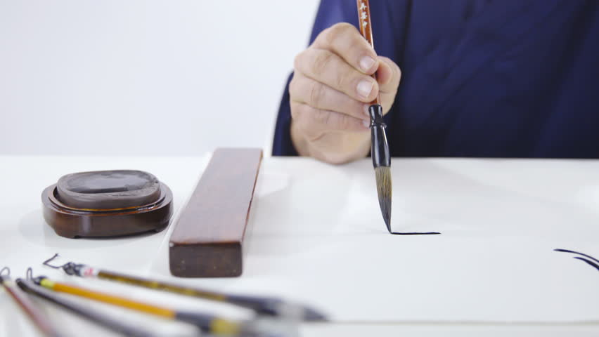 Wisdom inteligence and tradition in drawing Chinese traditional calligraphy 4K. Dolly slide shot over table with big white paper and male person hand holding brush in focus. Drawing symbols on paper.