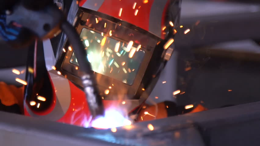 Man welder welds the parts of the structure in slow motion. Guy in orange protective mask working. Good skill. Cool welder makes a lot of sparks. Man in glasses makes a dangerous job slowmotion.