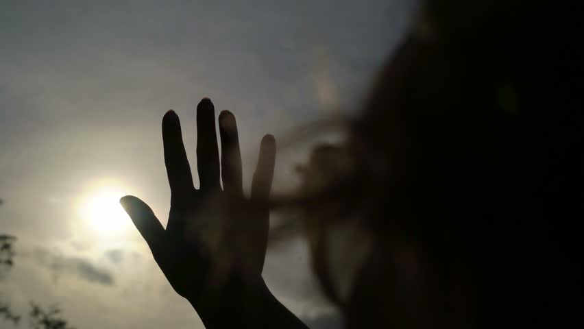 Woman catching the sun by hand silhouette   Shutterstock HD Video #24643028