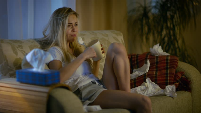 In the Evening Heartbroken Girl Sitting on a Sofa, Crying, Using Tissues, Eating Ice Cream and Watching Drama on TV. Her Room is in Mess. Shot on RED EPIC-W 8K Helium Cinema Camera.