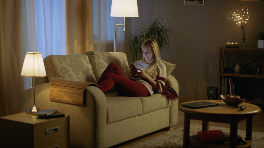 In the Evening Beautiful Young Woman Lies on the Couch and Uses Smartphone. Room Looks Warm and Cozy.  Shot on RED EPIC-W 8K Helium Cinema Camera.