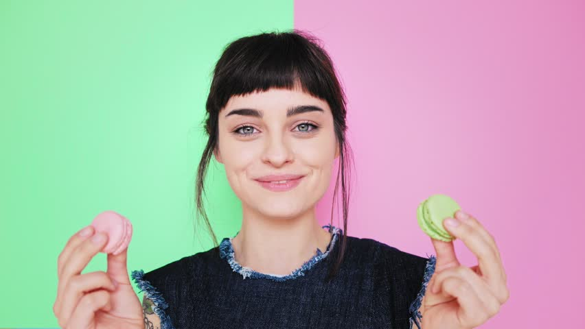 Attractive smiling young brunette isolated on splitted pistachio and rose red background holds two tasty cookies in her hands and makes her choice, then bite left macaron in pastel pink color