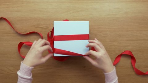 Aerial footage of woman opening red ribbon on gift. Lockdown shot of female unpacking present on wooden table. Personal perspective of lady receiving surprise during occasion.