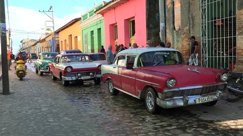 CUBA, - NOVEMBER 06: Hard road traffic with old American cars on the narrow Trinidad cobbled street. November 06, 2016 in Trinidad, Sancti Spiritus, Cuba