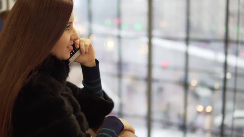 Young woman talking on the phone near the window in the mall | Shutterstock HD Video #24747776
