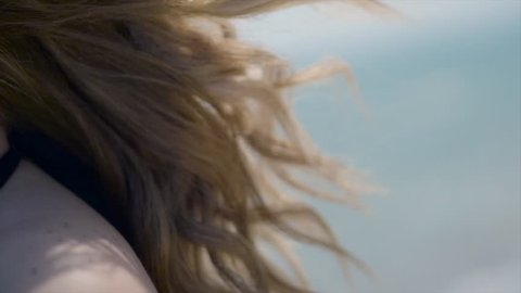 Wind blows girls blonde hair on tropical beach in Super slow motion