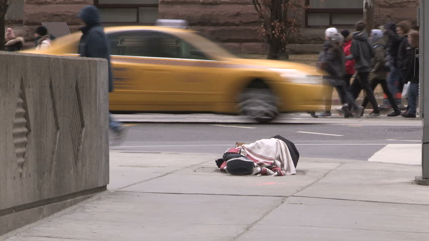 Toronto, Ontario, Canada March 2017 Homeless person lying on city street on cold winter day in Toronto