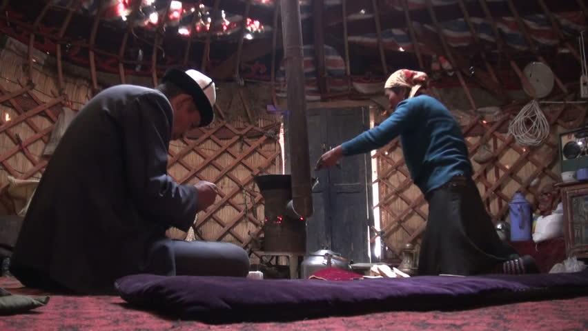 KARAKUL - SEPTEMBER 26 2010: A Kyrgyz family are preparing dinner inside a traditional yurt in Western China