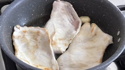 Time lapse of cooking slice of chicken with olive oil, thyme and garlic in a pot