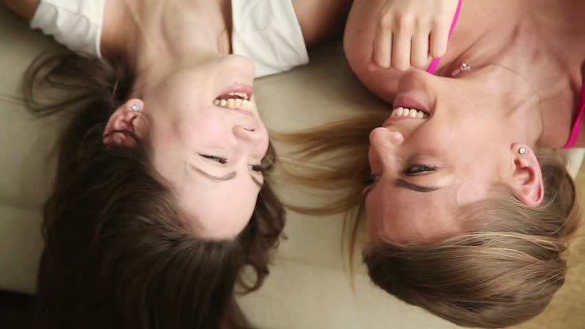 Top view of two joyful beautiful teen girlfriends hanging out at home, talking and laughing loud. Best friends having fun, spending time together lying on sofa and telling each other funny stories.