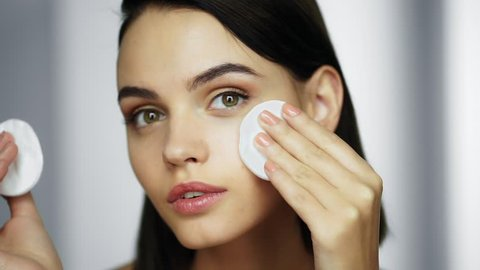 Beautiful brunette woman using cotton pads. Woman removing makeup. Beauty & Skin care concept. Close up