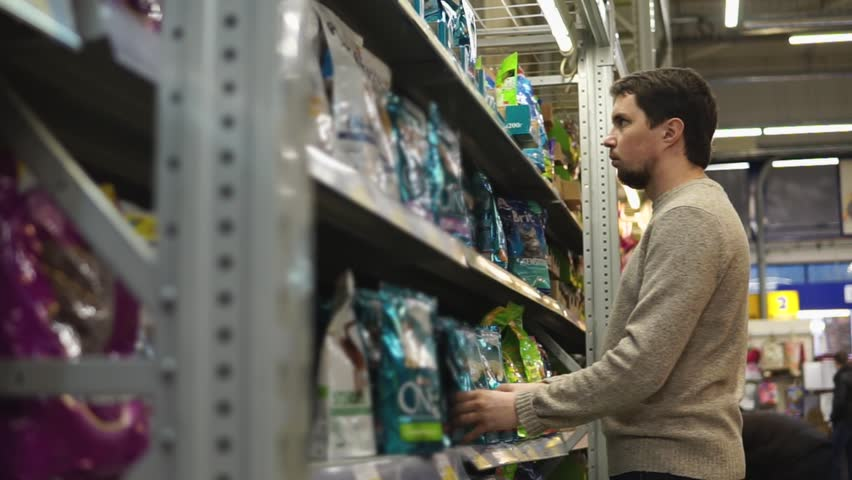 Young man chooses dry food for his dog or cat in the supermarket.