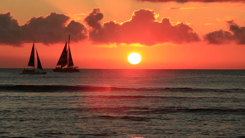 Sailboats cross the horizon during a pretty golden sunset in Hawaii.