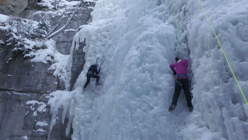 Aerial - Woman and Man ice climbers on ice wall dynamic shot - Maligne Canyon, Canada
