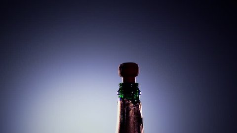 Bottle champagne wine is opened. Slow motion, lit background