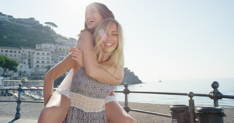 Two girl friends giving piggyback on vacation Tourist woman laughing and walking on beach promenade on summer holiday European travel adventure Amalfi Coast Italy