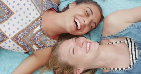 Top view of teenage girl friends lying on back smiling laughing at beach direct from above