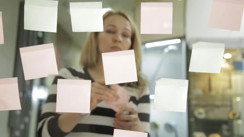 Creative businesswoman preparing to brainstorming session in modern glass office. Uses different colour stickers | Shutterstock HD Video #24935348