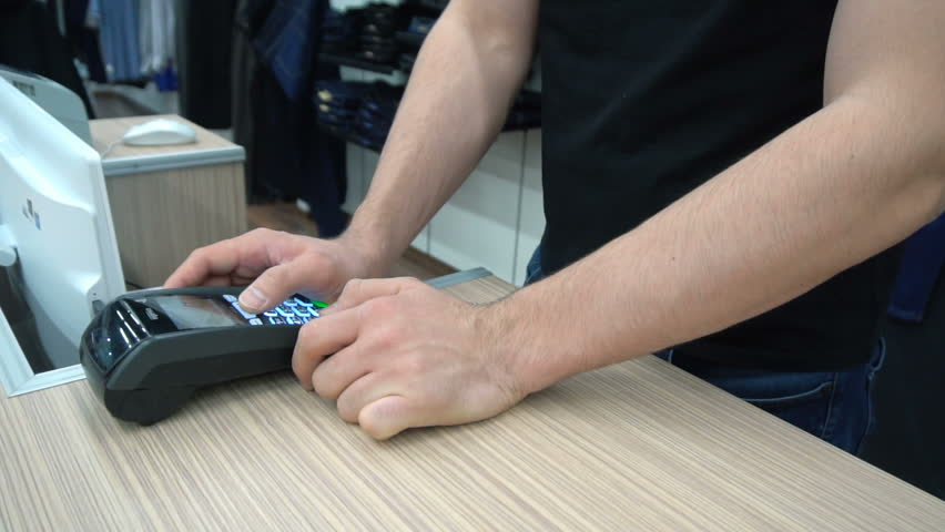 Side view of unrecognizable male shop assistant use card terminal behind the counter | Shutterstock HD Video #24941918