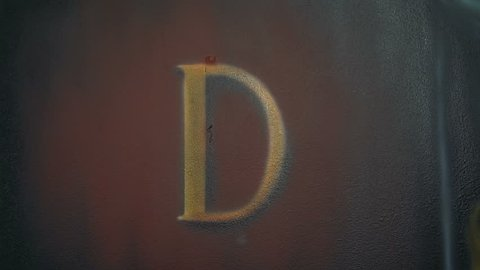 Letter D the gold graffiti on the wall