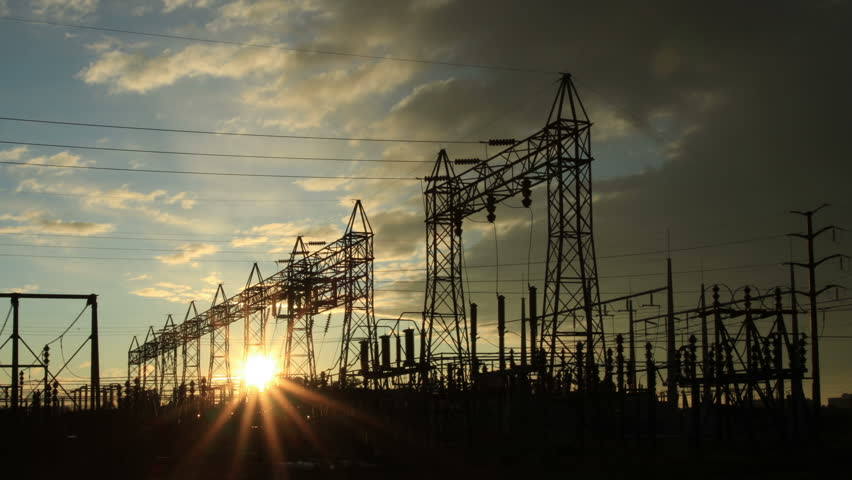Electrical power station, with the rising sun and storm clouds. HD 1080p time