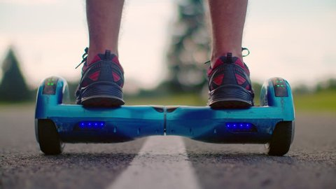 Man start moving on gyro scooter at asphalt road. Closeup of man legs on self balance hoverboard outdoors. Man riding on electric hover board at road