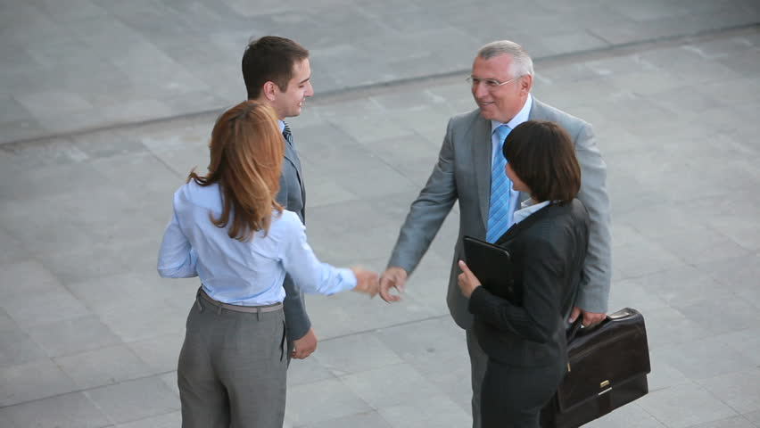 Positive business people shaking hands with their new partners and leading them away