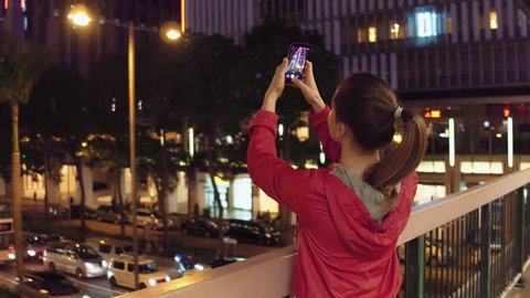 Young woman taking photos of buildings on her phone at night, Hong Kong.