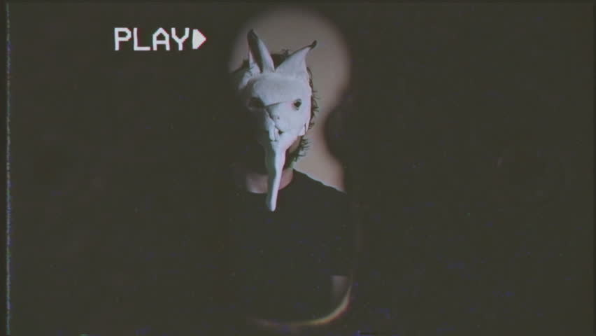 Fake VHS tape: through a keyhole we see an evil man (a crazy psycho killer) wearing a bunny mask, he comes close, his hands slowly grab us. Scary spooky horror halloween themed shot.