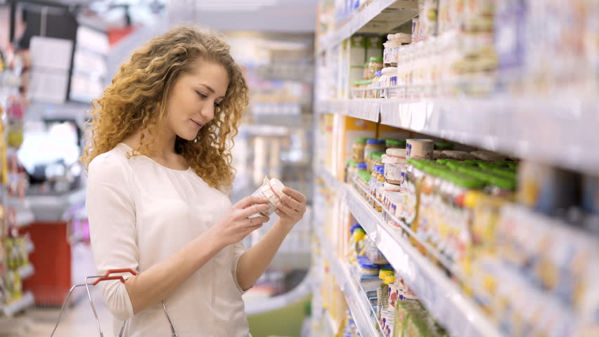 Cute 30s brunette model with long curly hair makes purchases in department store close up. Young mom selects puree, juices for child and puts baby food in basket holding hand. Consumer society concept