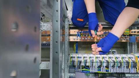 Factory electrician engineer installing cables with screwdriver, tighten the nut in electical box control cabinet into fuse box.