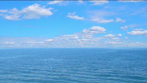 Sea view on the nice summer day, clean blue water and smooth waves, blue sky with clouds, horizon line. Sea, ocean, nature timelapse video background.
