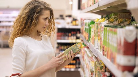 Woman chooses juice in the supermarket. Woman Choosing Products in Shopping Mall. Girl stands near the store shelf and selects the products