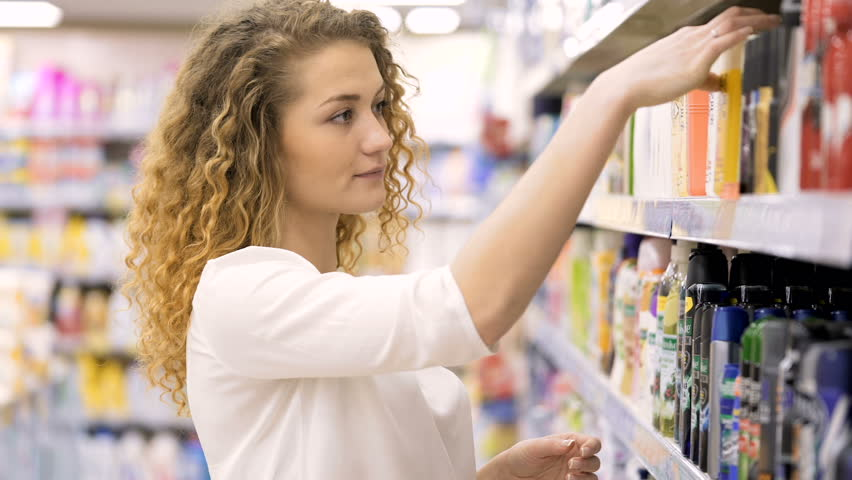 Beautiful woman looking at cosmetics in supermarket. Attractive girl buying cosmetic products. Looking and choosing. choosing cosmetic cream in beauty shop