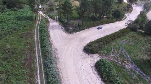 Aerial follow shot of Subaru Rally car accelerating along dirt track