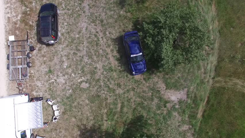 Aerial overhead shot of blue subaru rally car and people below