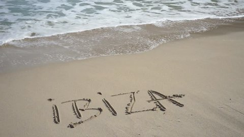 Ibiza written in sand beach washed away from waves, summer holiday concept.