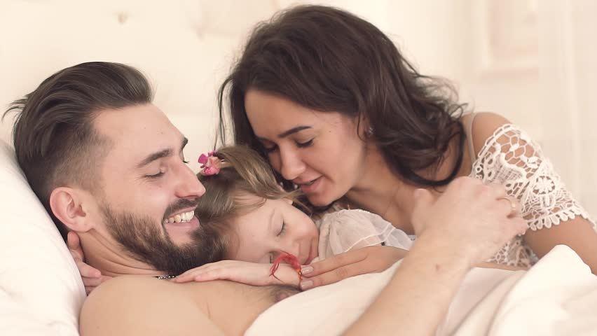 Happy family in bed waking up cute little daughter   Shutterstock HD Video #25036988