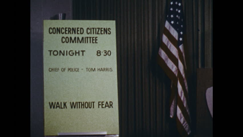 UNITED STATES: 1960s: walk without fear title. Door of Police Office. Man stands at podium by American flag | Shutterstock HD Video #25050551