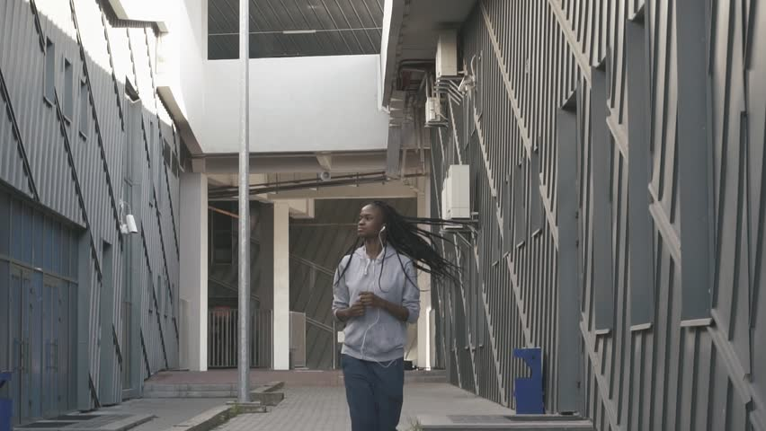 The jogging of the athlatic afro-american woman along the buildings. The model is listening to music   Shutterstock HD Video #25058468